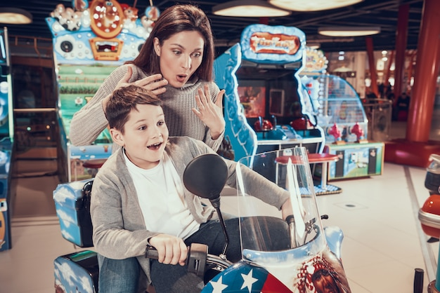Mom and son in amusement park on toy motorcycle.