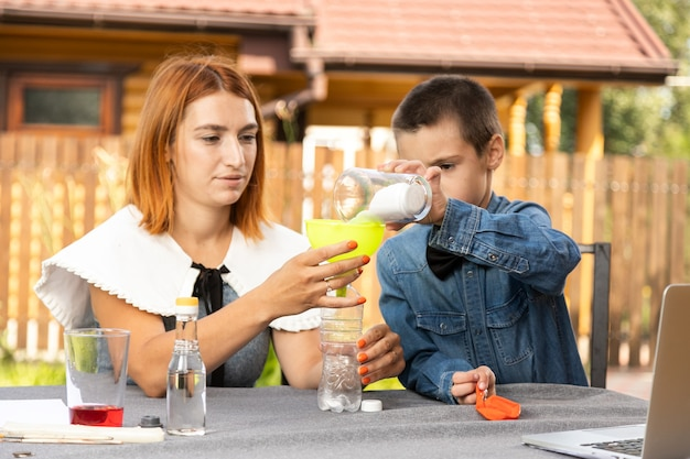 Mom and son are conducting chemical experiments at home. an experience with a child about creating a rocket launcher using a bottle, soda and vinegar.