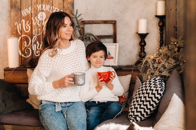 Mom and son are sitting at home on the couch with a gift and coffee in their hands.happy family