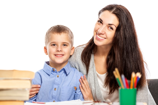 Mom and son are smiling and hugging while doing their homework. love and tenderness. white background.