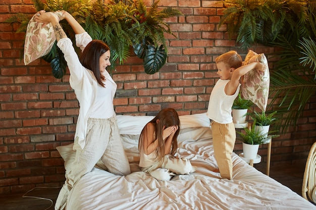 Mom son and daughter fight on pillows on the bed in the bedroom