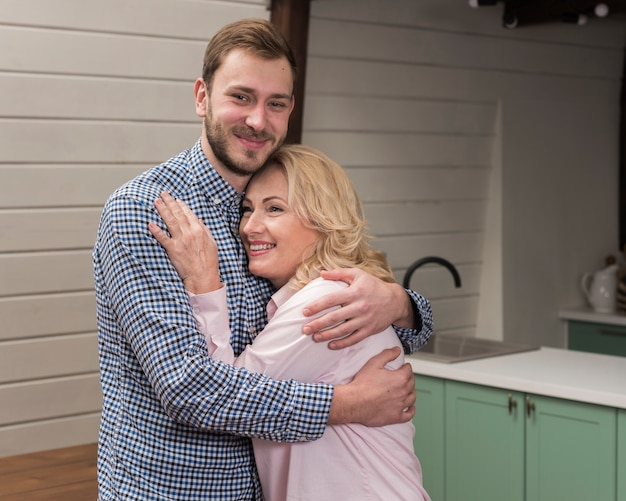 Mom and son embraced in the kitchen