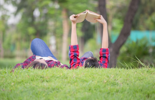 Mom and son lying on the grass and reading a book