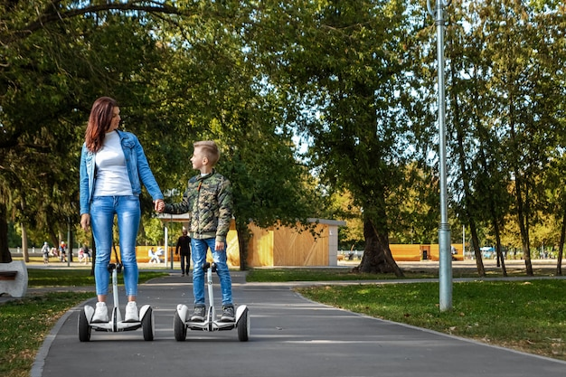 Mom and son ride a hoverboard in the park