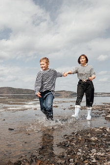 Mom and son on the river bank. mom and son in vests and rubber boots run merrily on the water. family intimacy in the open air. recreation and lifestyle.