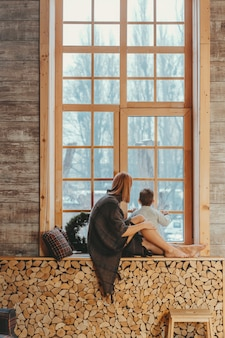 Mom and son sitting on the windowsill and playing.