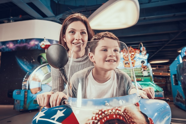 Mom and son on toy motorcycle spending holiday together.