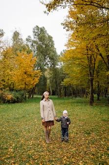 Mamma e figlio che camminano e si divertono insieme nel parco d'autunno.