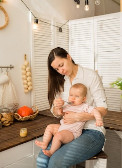 Mom spoon feeds a little baby girl in the kitchen