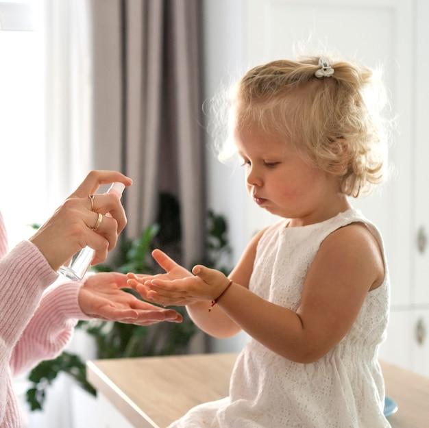 Мама распыляет дезинфицирующее средство для рук на руки ребенка дома