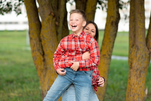 しゃがんでいるお母さん、笑顔の息子を抱きしめます。あらゆる目的のために。