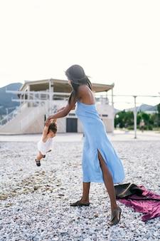 ママはビーチに立って、腕で小さな女の子を振ります