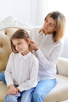 Mom straightens her daughter's hair
