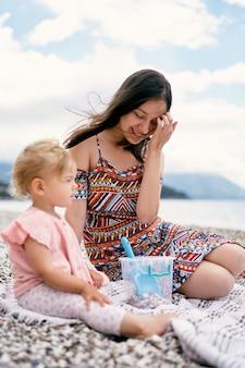 엄마는 해변의 침대보에 어린 소녀와 함께 앉아 있는 동안 바람에 머리를 곧게 펴다