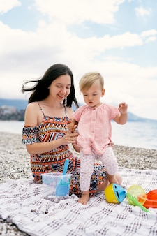 자갈 해변에서 침대보 위를 걷는 어린 소녀를 지지하는 엄마