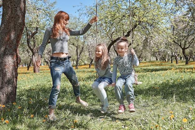 Мама качает детей на качелях в саду