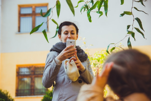 Мама фотографирует дочь на смартфон. женщина с темными волосами в серой одежде использует камеру своего телефона, чтобы сфотографировать своего маленького ребенка в теплый осенний день. семья проводит время вместе.