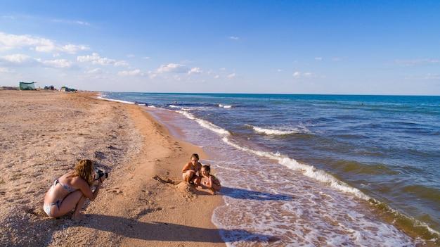 엄마는 azov sea의 배경에서 딸 사진을 찍습니다.
