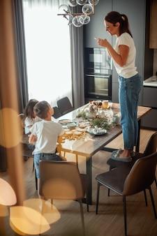 Мама фотографирует вид сверху, как дочь и сын украшают имбирные пряники сахарной глазурью стильный дом ...