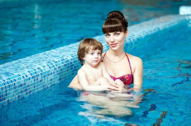 엄마는 아이에게 수영장에서 수영을 가르칩니다.