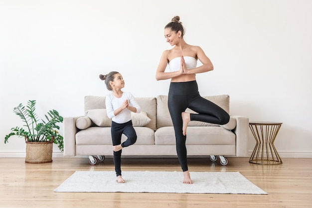 Mom teaches her daughter to play sports since childhood. yoga at home with family