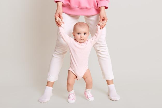 Мама учит дочь ходить, безликая женщина в белых штанах держит ребенка за руки и ходит в помещении против белой стены, ребенок смотрит в камеру и любит ходить.
