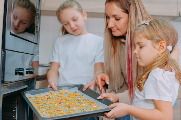 Mom teaches her daughters to cook in the kitchen.