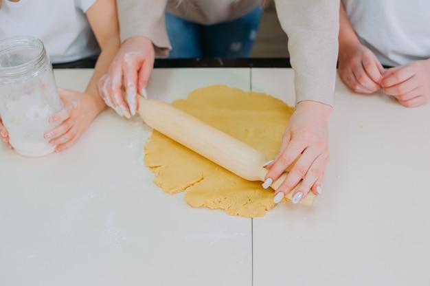 엄마는 딸에게 부엌에서 반죽을 요리하도록 가르칩니다.