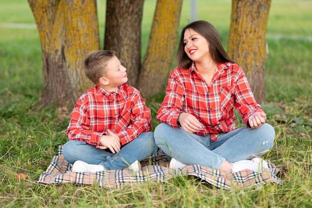 ママは息子に自然の中でヨガを教えています。あらゆる目的のために。