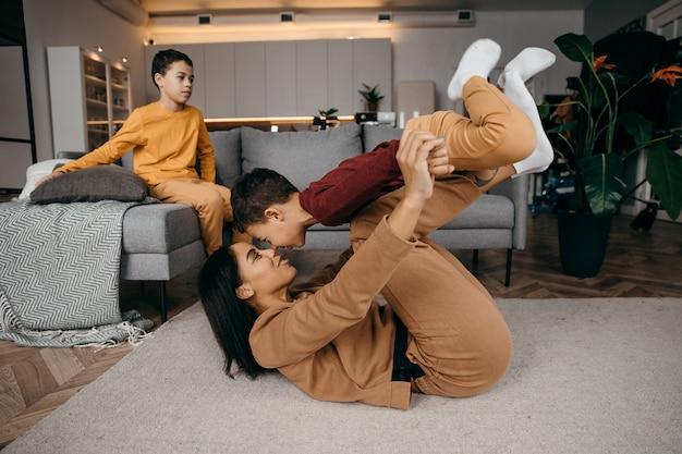 ママは2人の息子に朝の自宅でスポーツの体操をするように教えています