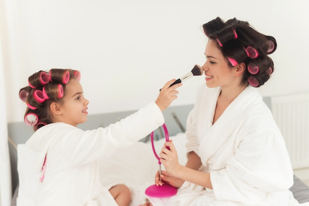 Mom teaches a little daughter to do makeup.