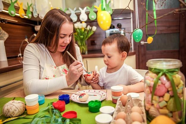 엄마는 아들이 장식 된 부엌에서 부활절 달걀을 칠하도록 가르치고 있습니다.