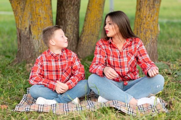 ママは芝生で息子にヨガを教えています。あらゆる目的のために。
