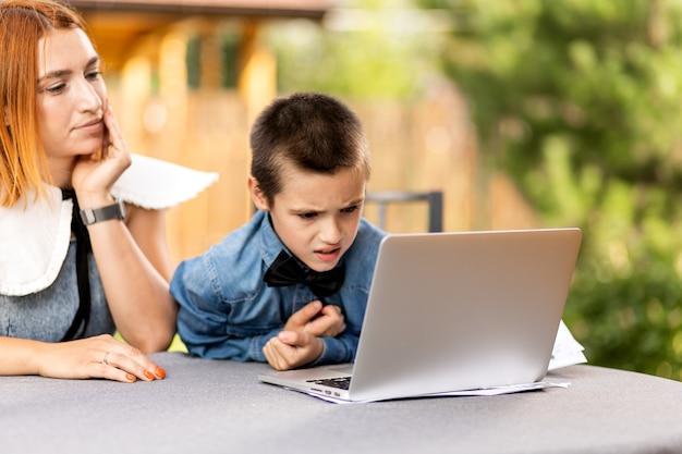 엄마는 집에서 정원, 홈 스쿨링에서 아이를 가르칩니다. 엄마는 아들이 숙제를 하고 스트레스를 받도록 도와줍니다. 노트북을 통한 온라인 학교 수업