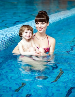 Mom teaching a child to swim in the pool
