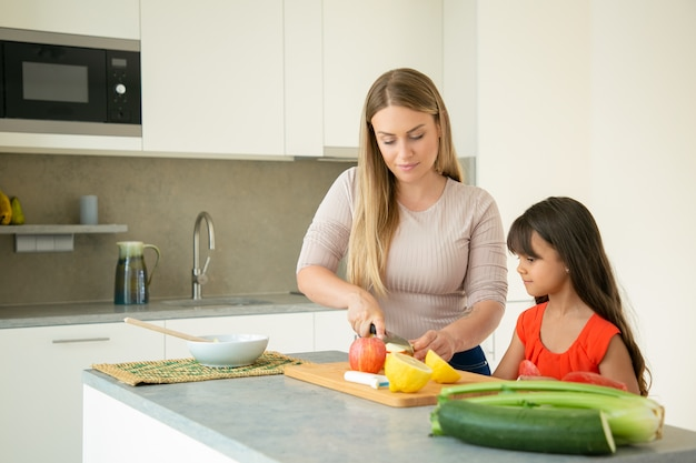 Mom teaching daughter to cook. girl and her mother cooking together, cutting fresh fruits and vegs on chopping board in kitchen. family cooking concept