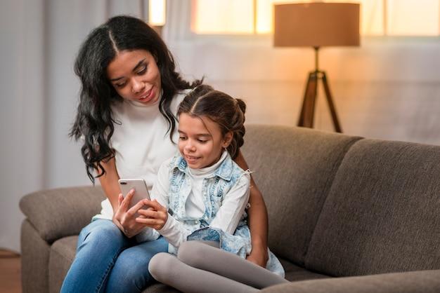 Мама учит дочь пользоваться мобильным телефоном