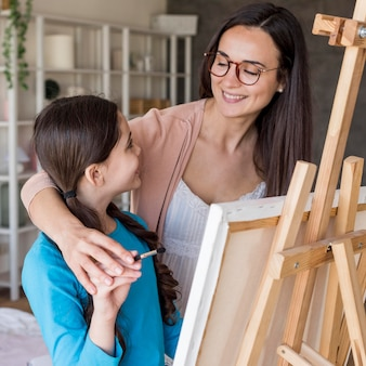 Mom teaching girl to paint at home