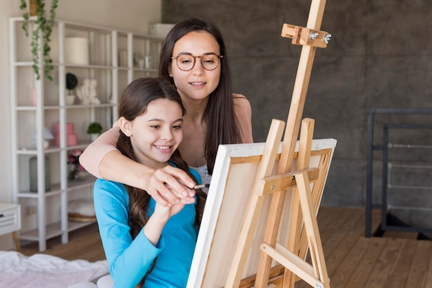 Mom teaching girl to paint