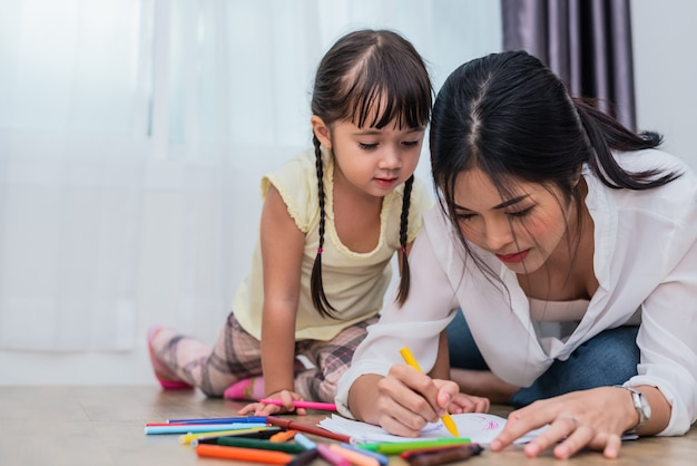 Mom teaching her daughter to drawing in art class. back to school and education concept