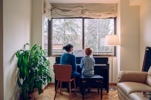 집에서 피아노 레슨을하는 아들을 가르치는 엄마. 실내에서 함께 시간을 보내는 가족 생활. 음악적 미덕과 예술적 호기심을 가진 아이들.