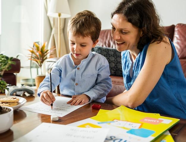 宿題をしている息子を教えるママ