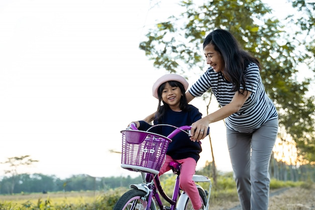 Mom teaching her toddler daughter to learn bicycle