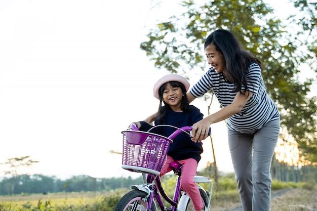 자전거를 배우기 위해 유아 딸을 가르치는 엄마