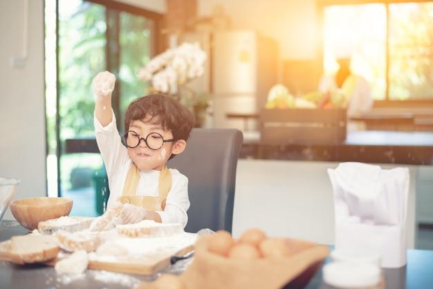 お母さんが子供に料理を教えています。粉とパンで材料を準備します。