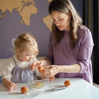 Мама учит маленького ребенка готовить, проводя время дома