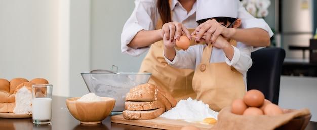 음식을 요리하는 아들을 가르치는 엄마. 집에서 엄마와 아이의 일상 생활 방식. 부엌에서 함께 아시아 가족입니다.