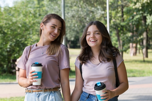 Mom and teenage daughter have fun on a walk in the park. happy family concept