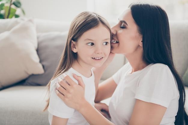 Mom tell small kid girl secret in house indoors