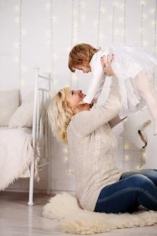 ママは、保育園の床に座って、娘を投げます